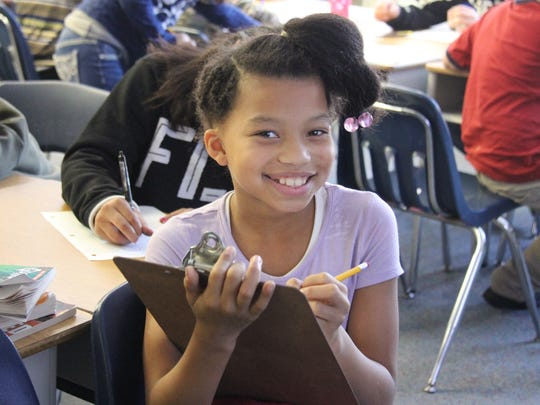 Hamilton Elementary School fourth-grader Kayla Beard is all smiles as she composes her letter to a U.S. Marine before Christmas. Now it's even easier to send a letter to military overseas.