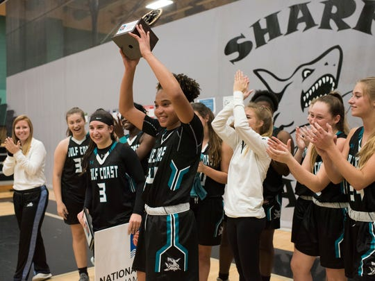 Yasmeen Chang, center, celebrates winning the tournament MVP award after Gulf Coast beat Ursuline Academy to win the National Division championship game of the Naples Holiday Shootout tournament at Gulf Coast High School on Saturday, Dec. 30, 2017.
