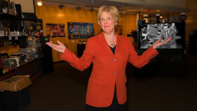 WITF President and CEO Kathleen Pavelko poses in front of Tech Tsunami, a display showcasing the station's 50-year history.  The display, located in the stations' atrium at 4801 Lindle Road in Harrisburg, is free and open to the public from 8:30 a.m. to 5 p.m. Monday through Friday.