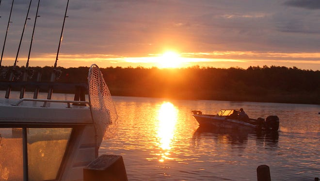 As the sun rises, anglers motor on the Rainy River toward Lake of the Woods.