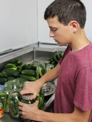 Austin Maile cans pickles at his home in Avon. The pickles are among approximately 30 products Maile sells under his Austin's Acres brand.