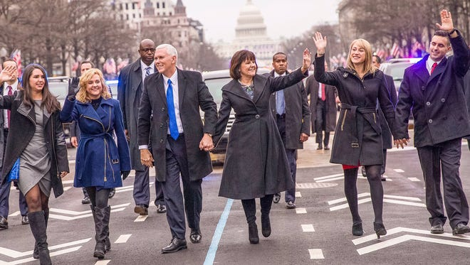Vice President Mike Pence and Karen Pence are shown walking with their family and waving to bystanders during the inaugural parade on Jan. 20, 2017.