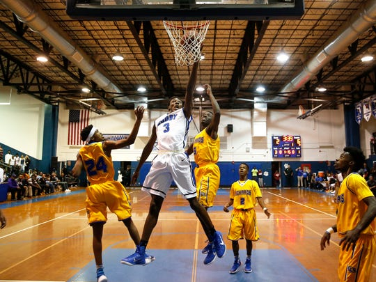 Godby's Quan Jackson drives to the lane for a layup between Rickards' Deandre Barnhart, left, and Cameron Enzor during their game at Godby on Friday.