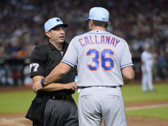 Home plate umpire Jim Reynolds (77) talks with New
