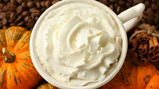A cup of pumpkin spice latte is pictured with pumpkin, cinnamon sticks and coffee beans.