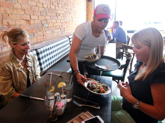 Jessica Krebs serves Mary Claire Brass (left) and Tara Halpin, both of Fort Thomas, at Packhouse Meats in Newport, where tipping is not permitted. Krebs said she likes the policy because each check contains a 20 percent gratuity.