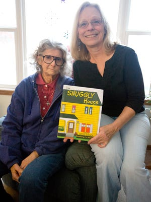 "Illustrator C.R. Macomber, left, and author of ""Snuggly House"" Gaylee Warner sit in Warner's living room in Wisconsin Rapids, Friday, Jan. 15, 2015."