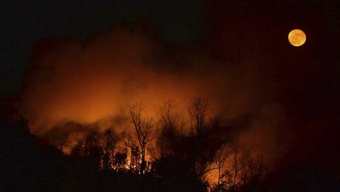 A wildfire burns Tuesday as it approaches Bat Cave, N.C. Thick smoke has settled over a wide area of the southern Appalachians, where dozens of uncontrolled wildfires are burning through decades of leaf litter.