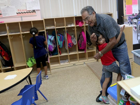German Cutino, a foster grandparent volunteer from the Community Place, gets a hug from 5-year-old Daniela Morales Negron during the prekindergarten summer program at Ibero Family Center.