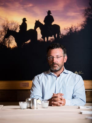 Nate Hopper, co-owner of Sierra Bonita Grill, sits in his Phoenix restaurant. Hopper explains that all the artwork in his restaurant depicts Arizona and the three prime groups in the West: Mexican, Native American, and Cowboys. The artwork is often provided by the artists and Nate has carefully selected each work of art.