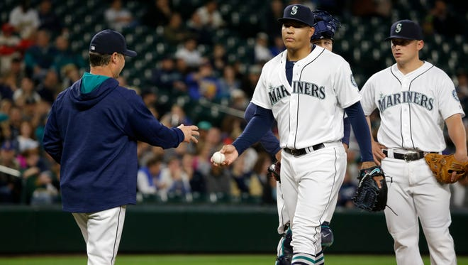 Seattle Mariners starting pitcher Taijuan Walker, second from right, is pulled in the eighth inning of a baseball game against the Oakland Athletics by Mariners manager Scott Servais, left, Monday, May 23, 2016, in Seattle.
