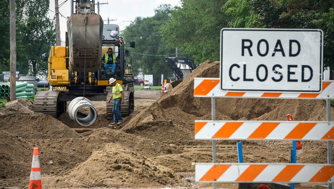Crews work in the afternoon heat on construction projects along Seventh Street North Friday, July 13, in St. Cloud.