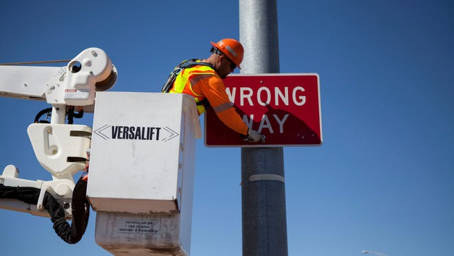 ADOT worker Daniel Gutierrez takes down an old wrong way sign to replace it with a larger one.