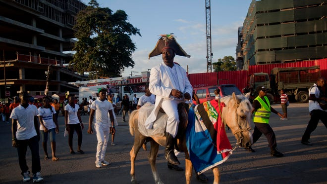 A man dressed as Haitian national hero Jean-Jacques Dessalines rides his horse, draped with a Haitian national flag, to the site of a high-voltage wires' accident that left at least 16 people dead, to attend a vigil honoring the victims, in Port-au-Prince, Haiti, Tuesday, Feb. 17, 2015.