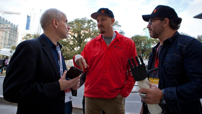 Mick Ebeling and Elliot Kotek show off a prosthetic arm printed by a 3-D printer.