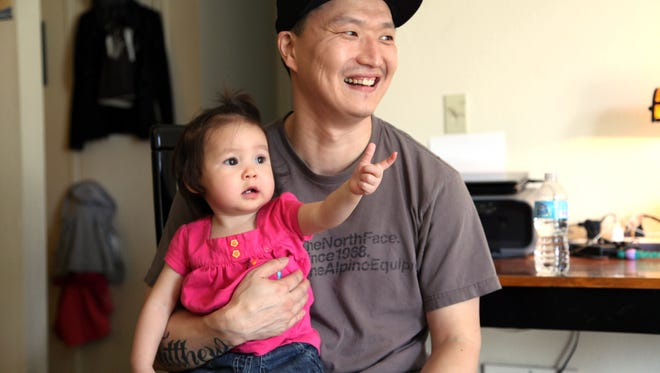 Korean adoptee Adam Crapser  poses with daughter, Christal, 1,  in the family's living room in Vancouver, Wash. on March 19, 2015.   Crapser, whose adoptive parents neglected to make him a U.S. citizen, will face an immigration judge and could be separated from his family and deported to South Korea, a country he does not know. (AP Photo/Gosia Wozniacka)