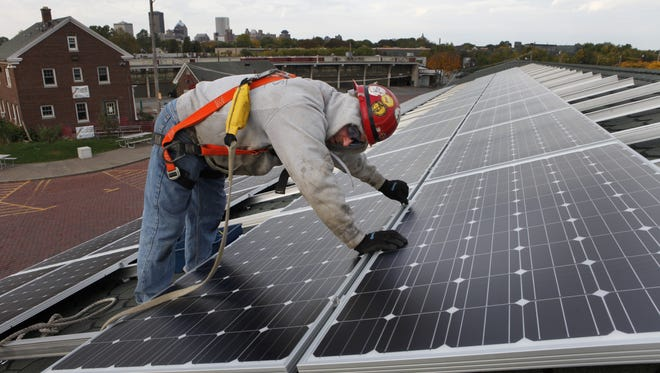 Mike Dertinger of Invictus Electrical installs solar panels on one of the sheds at the Rochester Public Market in October 2012.
