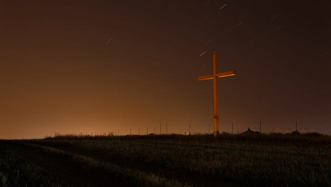 """FILE-This photo taken May 3, 2013, shows a long time exposure showing the stars in the sky over a cross of """"Panagia Chrisospiliotissa"""", a Christian Orthodox monastery outside of capital Nicosia, Cyprus. The number of Americans who don't affiliate with a particular religion has grown to 56 million in recent years, making the faith group researchers call """"nones"""" the second-largest in total numbers behind evangelicals, according to a Pew Research Center study released Tuesday, May 12, 2015. (AP Photo/Petros Karadjias, File)"""