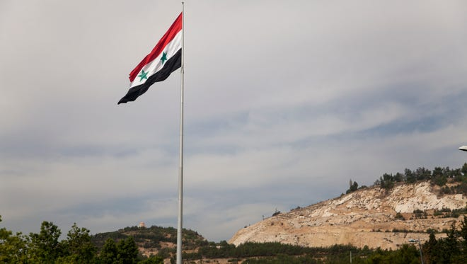 FILE - In this Monday, Oct. 27, 2014 photo, a Syrian flag flies over the capital, Damascus, Syria.
