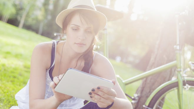 Beautiful girl using tablet in park