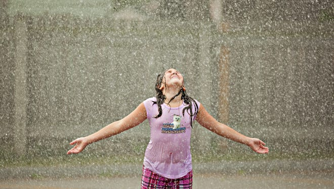 """A young girl lets water from a fire hydrant cool her off during one of the city's """"Cool Sweep"""" days in recent years."""