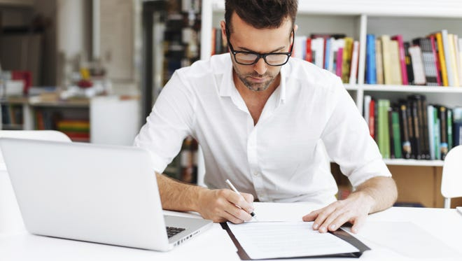 Man taking notes from online course.