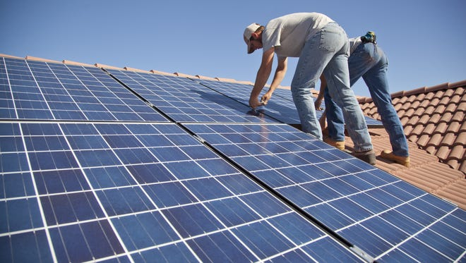 Technicians from Legend Solar install solar panels on a St. George home Friday, March 20, 2015.