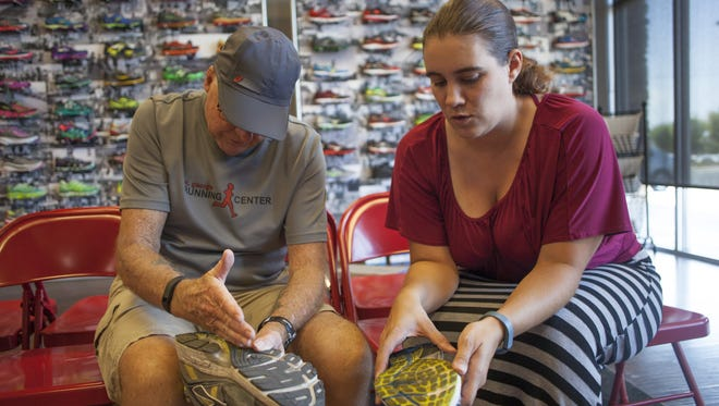 Ted Cooley, an employee at the St. George Running Center, fits Spectrum Audience Analyst Casie Forbes to proper running shoes and gives her training tips leading up to the St. George Marathon Friday, Aug. 28, 2015.