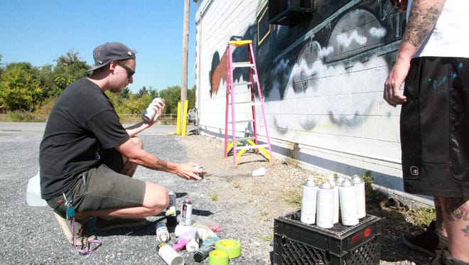 Ethan Donnelly of Staunton and Cody Brogan of Greenville (out of frame) work on a train mural on the side of Basic City Luncheonette, a Waynesboro institution, on North Commerce Avenue Thursday, September 17, 2015.