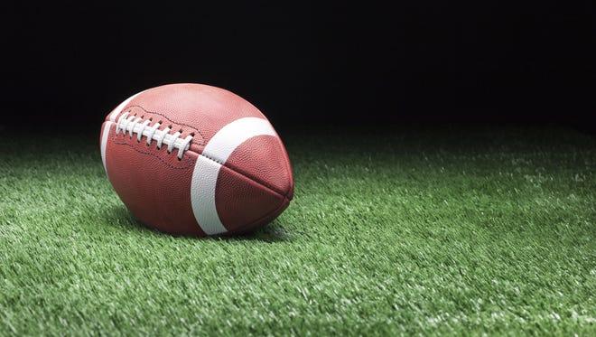 Football on grass against dark background