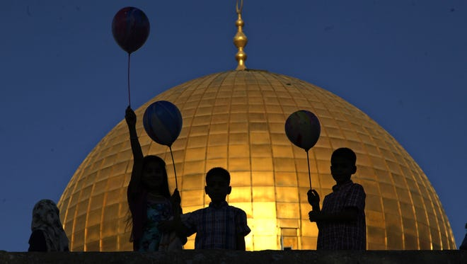Palestinian children hold balloons during the Muslim holiday of Eid al-Adha, near the Dome of the Rock Mosque in the Al Aqsa Mosque compound in Jerusalem's old city, Thursday, Sept. 24, 2015.