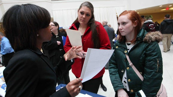 Newark residents Stefani Bultena (right) and her friend Kara Anglin (center) talk with Angela Davis of Citibank at the job fair.
