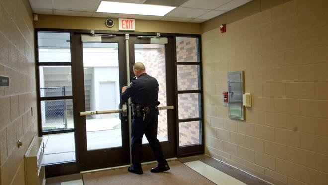 Police Officer Bryan Coleman checks to make sure a doorway is properly secured during a random routine walk-through Thursday, November 12, 2015 at Port Huron High School.
