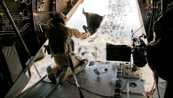 A Marine drops propaganda leaflets from a helicopter in Afghanistan.