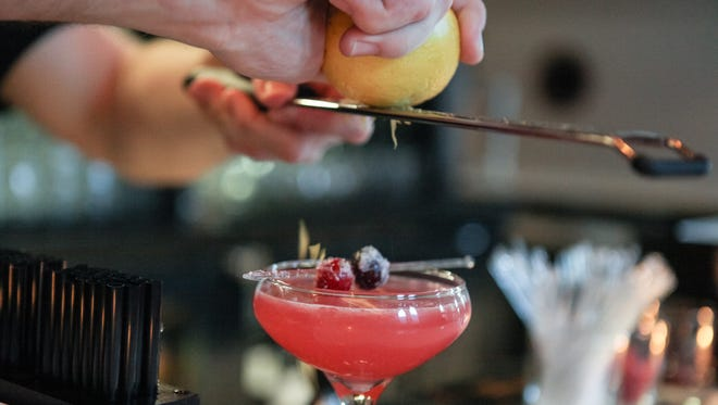 Lemon zest is shredded as finish on top of a Juniper Elixir at the Vestry Bar in OTR. The bar, located inside of the Transept is set to open Friday evening to the public at 7:30 p.m.
