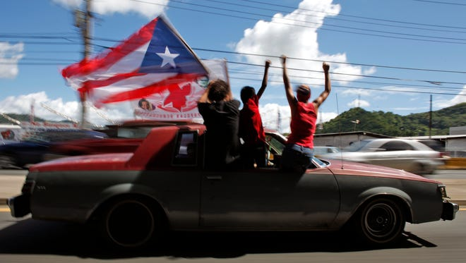 Demonstrators wave a Puerto Rican flag during elections in San Juan in November 2012. Voters cast ballots in a referendum on changing the island's relationship with the United States.