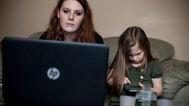 Kristen Suratt, 22, works on a Spanish course on her computer while her daughter Aurora, 4, sits with her and plays on a tablet Thursday, Jan. 14, 2016 at their Port Huron home. Suratt is going through the Michigan Works Young Professionals program to receive her high school diploma. After finishing her diploma, Suratt plans to pursue a a degree in health care.