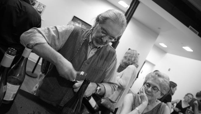"Wally ""The Wine Guy"" Plahutnik opens a bottle of wine at FilmScene during a Vino Verite event."