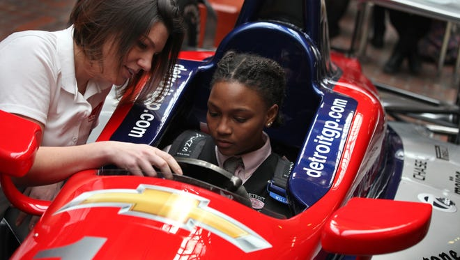 Grand Prix driver Katherine Legge  talks to Asia Anderson, 15, while she gets to sit in a Model Grand Prix racing car. Students in the science class at the International Academy for Young Women in Detroit  were treated to a visit from  Legge.