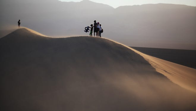 Visitors shield themselves from the wind blowing on Mesquite Flat Sand Dunes at Death Valley National Park on Tuesday, March 22, 2016 in Death Valley, Calif.