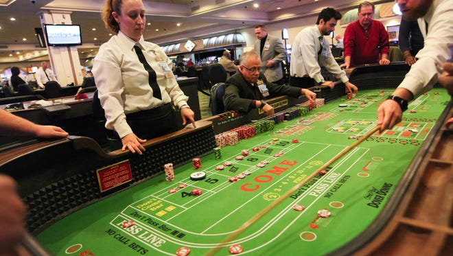 Players are seen at the craps table game at Dover Downs Hotel & Casino. The casino's parent company reported a $239,000 first-quarter loss on Thursday.