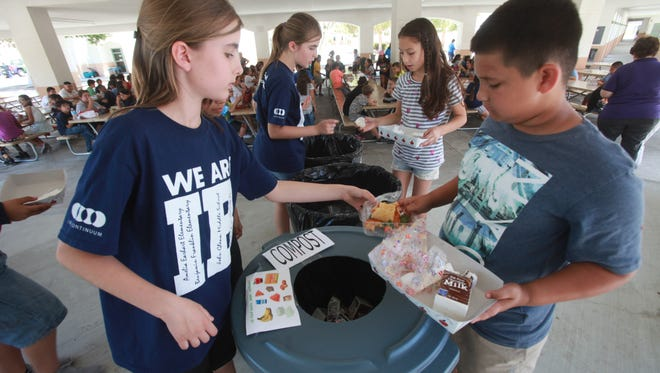 At left, twins, Lilli and Madeleine Koch, students at Benjamin Franklin Elementary School in La Quinta, help students sort out their trash. The twins have developed a system at the school where organic waste is separated as to not end up in the landfill and instead they want to create compost.