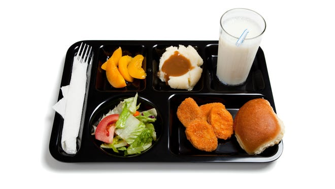 A black school lunch tray including tossed salad, chicken nuggets, roll, peaches, mashed potatoes and gravy with milk on a white background