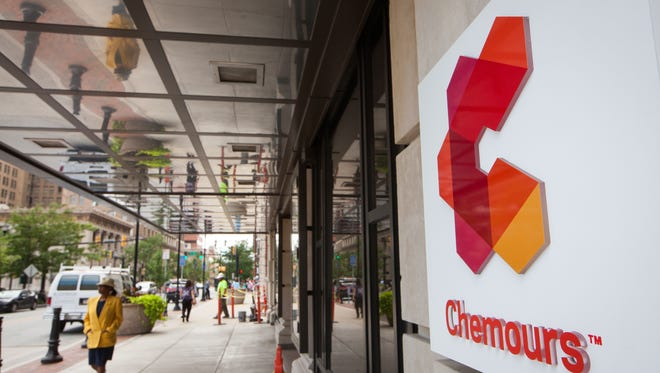 Pedestrians walk past the headquarters of Chemours in the DuPont Building in downtown Wilmington on June 30. Congress is exploring a chemical safety bill that would reform standards.