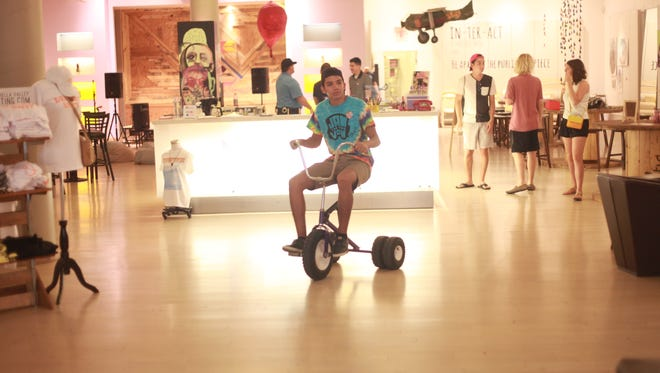 The Coachella Valley Art Scene has opened a new interactive pop up art and music space at Westfield Mall in Palm Desert. The venue holds free concerts, art activities and other interactive experiences. In this photo Jacob Gutierrez rides a tricycle as part of the experience.
