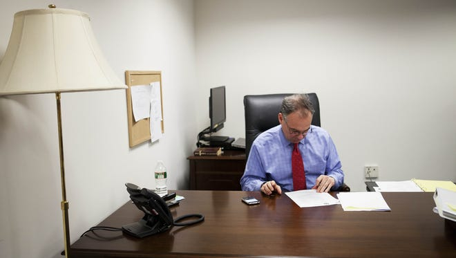 Sen. Tim Kaine looks at his Blackberry and some paperwork in his spartan temporary office in January 2013.