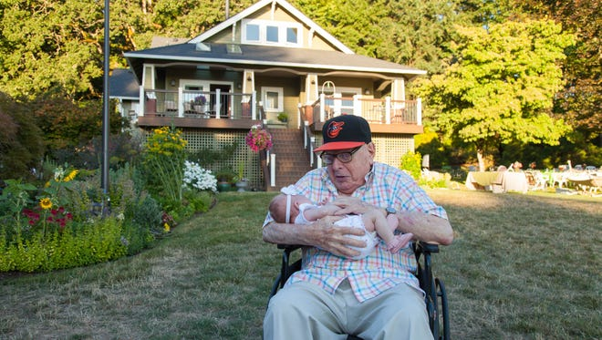 Like the house behind them, Paul Sachs, 98, and Mazie Jelsing, 6 weeks, demonstrate the beautiful juxtaposition of old and new.