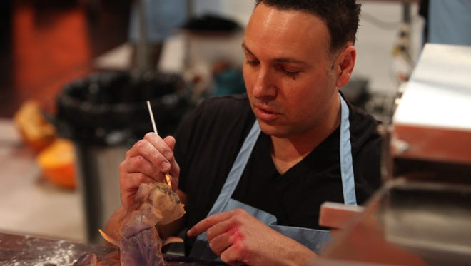 Al DiBartolo Jr., paints a piece of his 'Halloween Wars' creation. DiBartolo's team won the season competition on the Food Network.