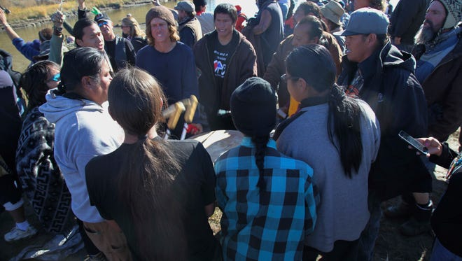 Demonstrators protest the expansion of the Dakota Access Pipeline under a water source close to the Stand Rock Sioux Reservation participate in a prayer and drum circle near Cannon Ball, N.D., Wednesday, Nov. 2, 2016. They were supporting others who stood in a tributary of the Cannon Ball River, seen behind, against a line of local police. Officers in riot gear clashed again Wednesday with protesters near the Dakota Access pipeline, hitting several dozen with pepper spray as they waded through waist-deep water in an attempt to reach property owned by the pipeline's developer. (AP Photo/John L. Mone)