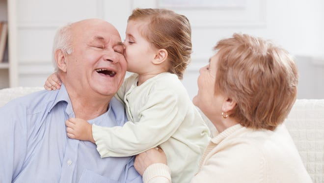 Pretty old men and women are spending time with their granddaughter. The girl is kissing her grandfather with joy. They are sitting on sofa and laughing